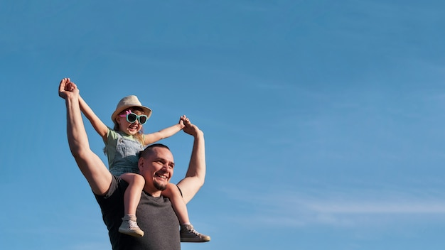 Father and daughter on shoulders happily rejoice. dad holding little daughter sitting on the flight mimics the father.