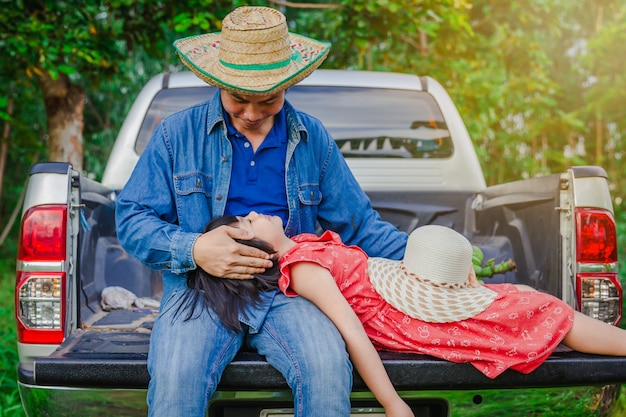 Father and daughter sit in the back of a pickup truck