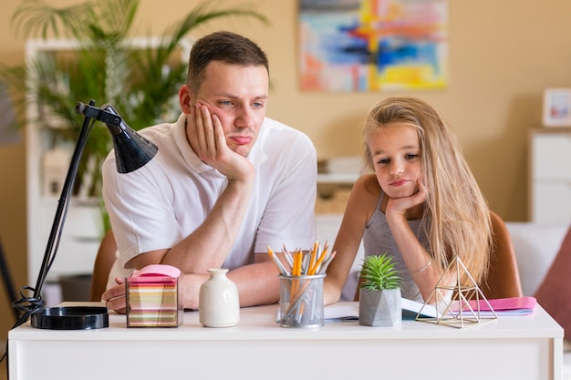 Father and daughter sitting at a desk
