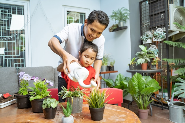 Father and daughter smiled happily while holding a watering can