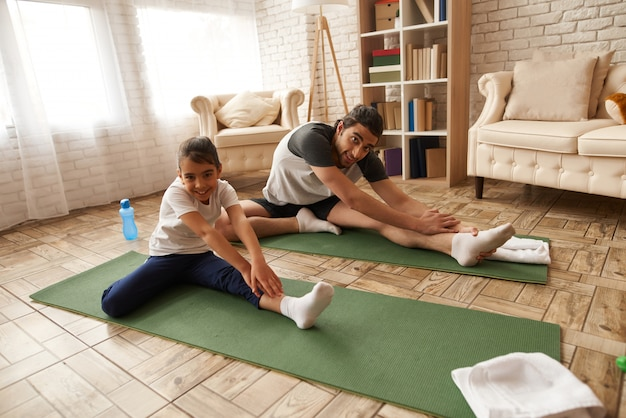 Father and daughter stretch legs on gym carpet.