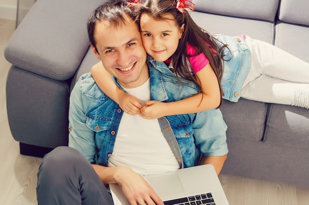 Father and daughter using laptop together at home