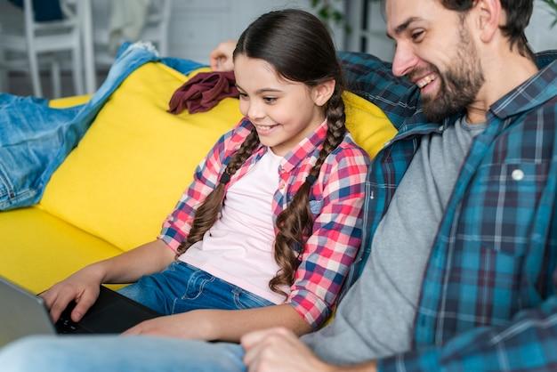 Padre e figlia che per mezzo di un computer portatile