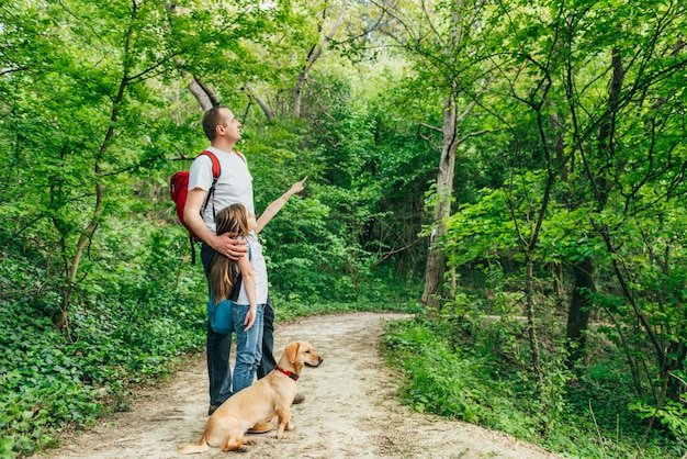 Father and daughter walking through the woods with dog
