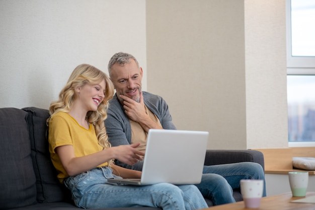 Father and daughter watching something on a laptop