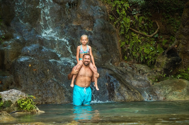 Father and daughter at a waterfall in the jungle. traveling in nature near a beautiful waterfall, turkey