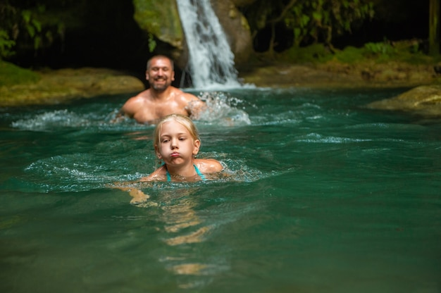 Father and daughter at a waterfall in the jungle.turkey