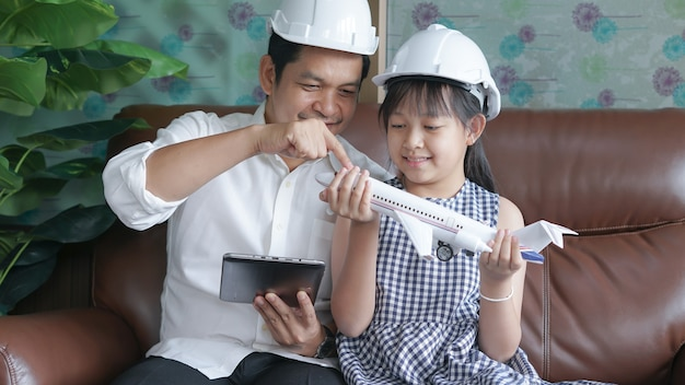 Father and daughter were wearing helmets and taught aerospace engineering with a tablet and toy airplane.concept of fathers day