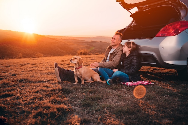 Father and daughter with dog camping on a hill by the car during sunset