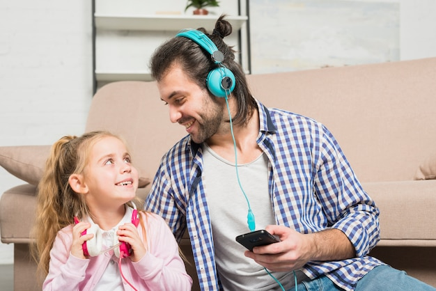 Father and daughter with earphones