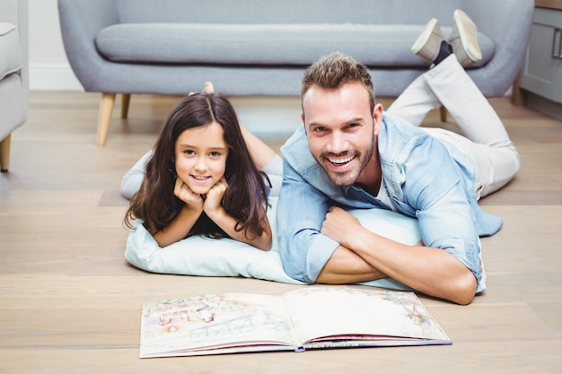 Father and daughter with picture book on floor