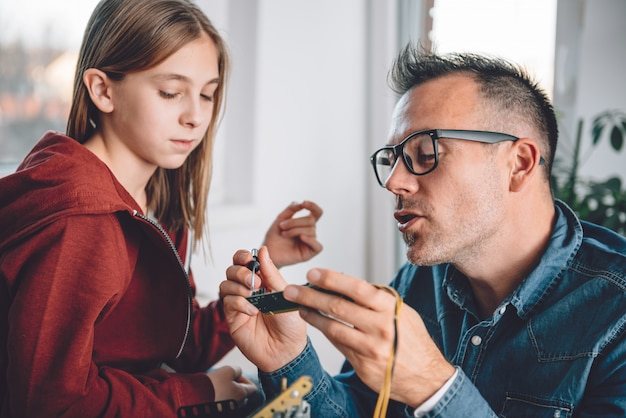 Father and daughter working together in workshop