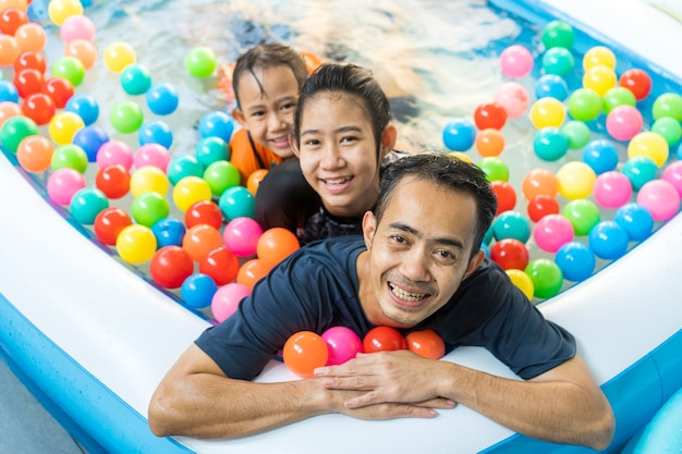Father and daughters playing in a swimming pool