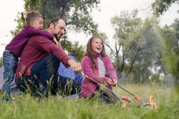 父、娘、息子は森のキャンプファイヤーでローストソーセージに座っています。父、親との余暇。幸せな家族の概念