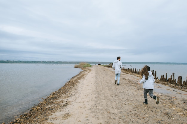 Father and dauther dressed in raincoat running near the lake and have a fun