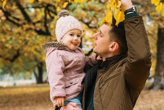 Father demonstrating his daughter autumn foliage in forest