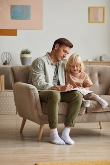 部屋のソファに座って絵を描くことを学んだ幼い息子と一緒にメモ帳に絵を描く父