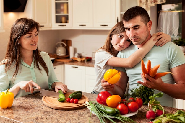 Father embraced by daughter in the kitchen while preparing food