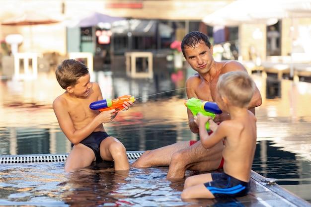 Отец наслаждается днем со своими детьми в бассейне