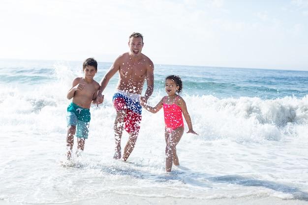 浅瀬で子供たちと楽しむ父