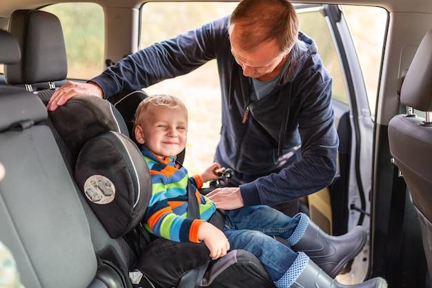父親が男の子の安全ベルトをチャイルドシートに固定している。