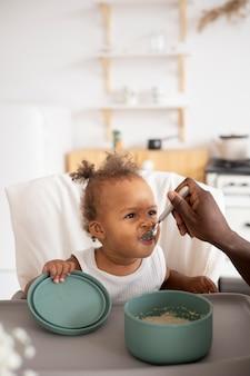 Отец кормит свою маленькую девочку на кухне