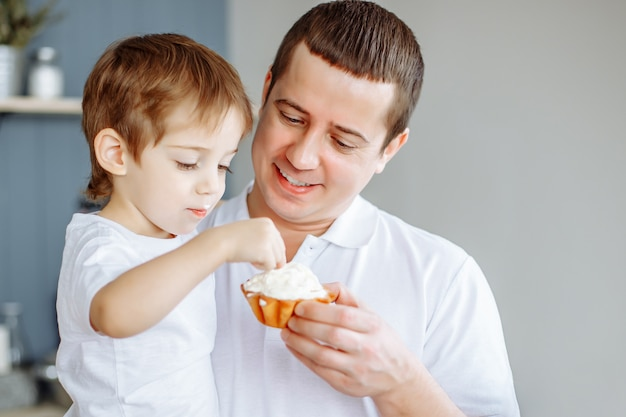 Father feeding his little son in kitchen.