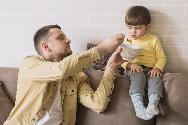 Father feeding his son in the living room