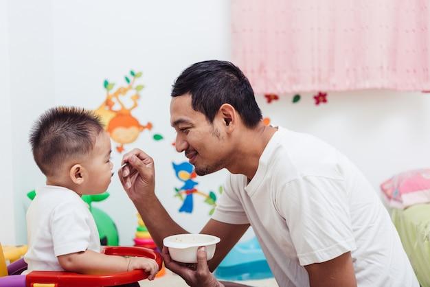 Отец кормит своего сына