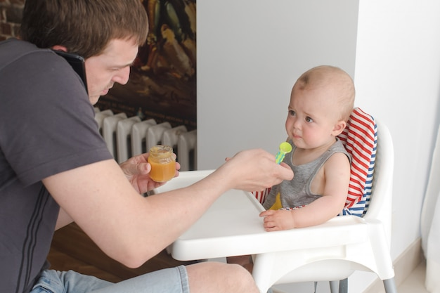 Father feeding infant son while talking phone