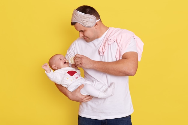 父は黄色い壁の上に孤立して立っている間哺乳瓶から粉ミルクを小さな娘に与えます