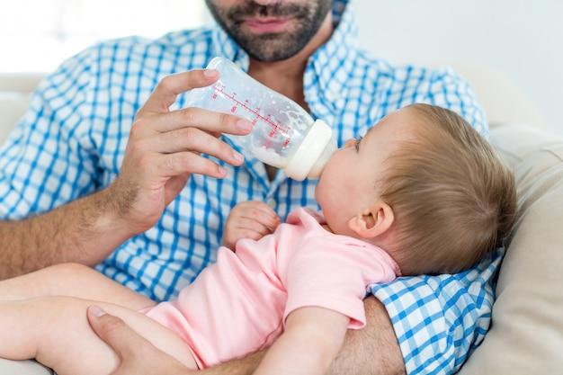 Father feeding milk to son on sofa
