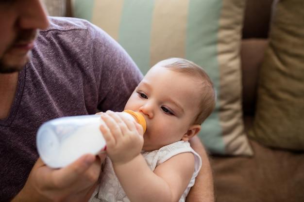 家で女の赤ちゃんにミルクを与える父