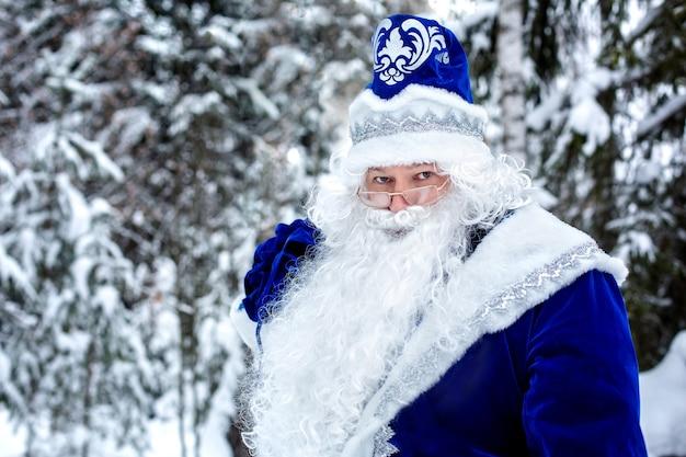 雪に覆われた木の中で、森の中で贈り物の袋を持ったフロスト神父。ロシアのジェド・マロース。