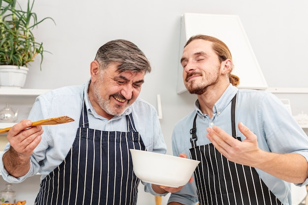 Father and funny son tasting a dish