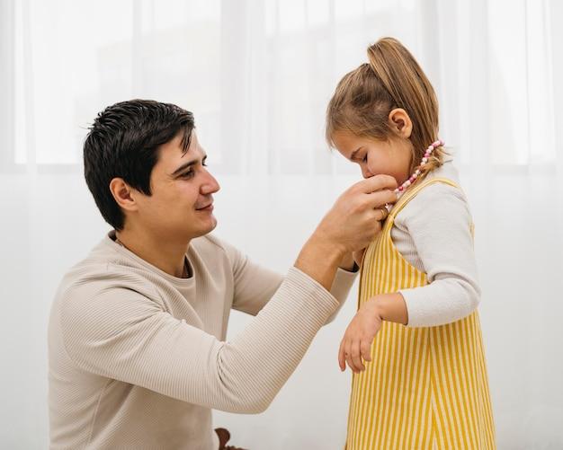 Padre che ottiene sua figlia vestita a casa
