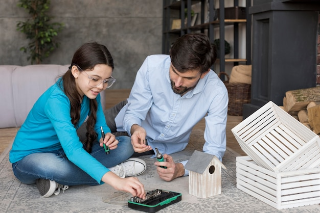 Father and girl building a bird house
