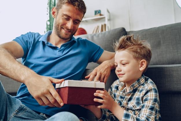 Отец дарит сыну подарок в коробке дома