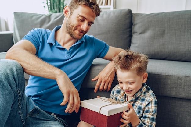 Отец дарит маленькому сыну подарок в коробке