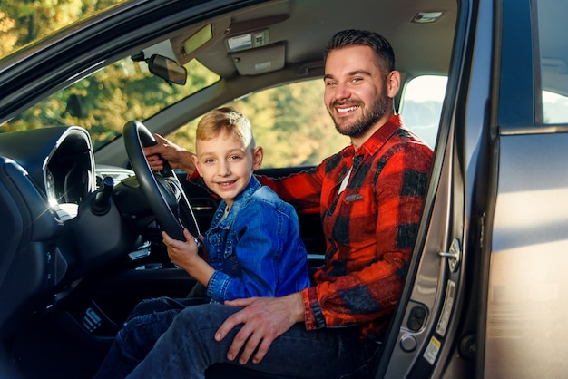 Father gives his son driving lessons, enjoying time together