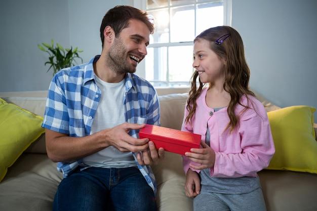 Отец дает подарок дочери в гостиной