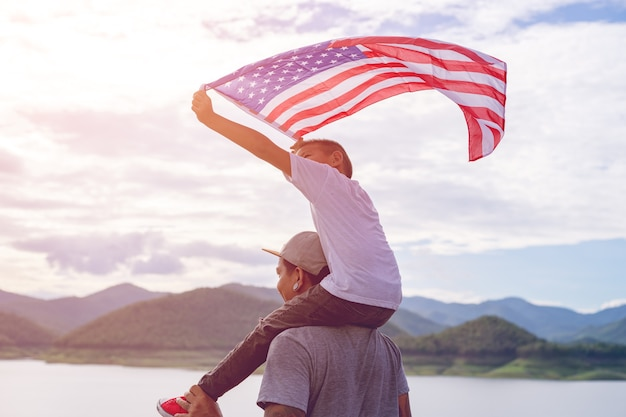 Father giving happy piggyback ride to his cute son with a hand held american flag in stand
