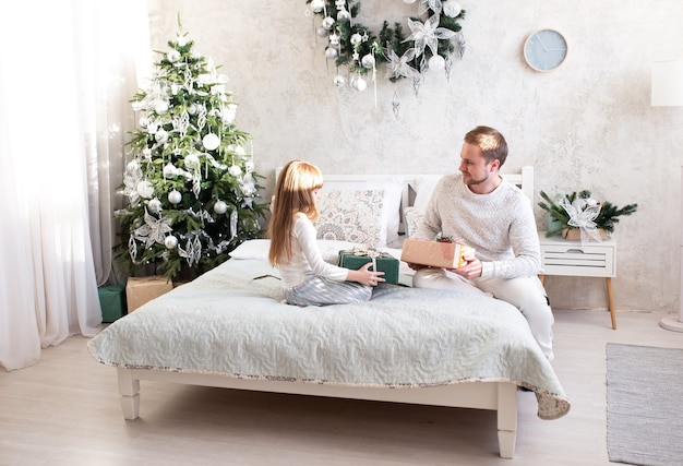 クリスマスツリーの近くの自宅のベッドで娘にギフトボックスを与える父