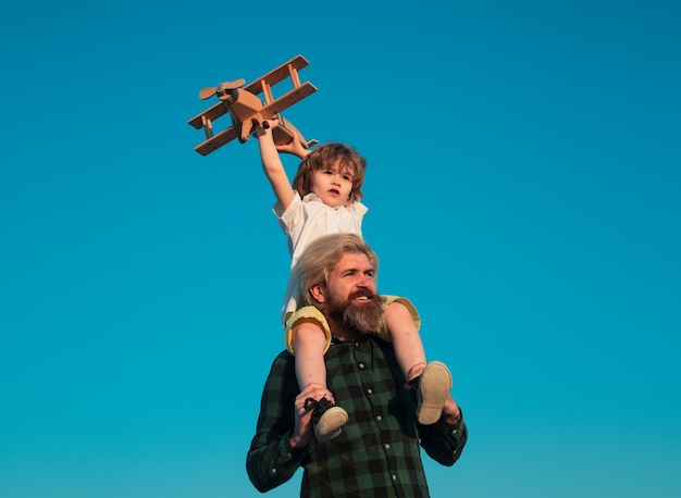 Father giving son ride on back in park. father and son playing with toy plane outdoor. family holiday, parenthood. fathers day.