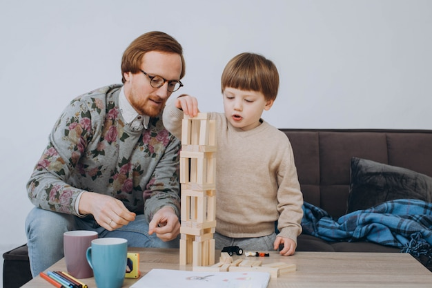 Father in glasses and adorable toddler son building wooden constructor tower.