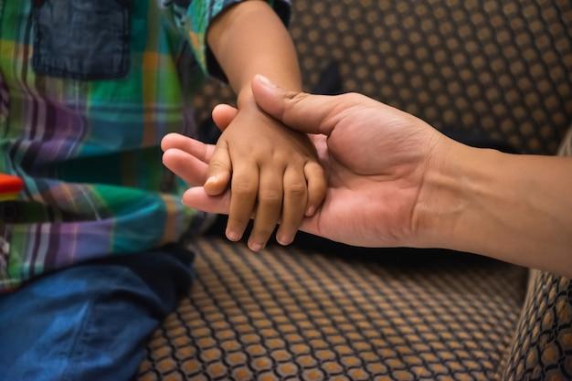 父の手は小さな子供の手を握ります。