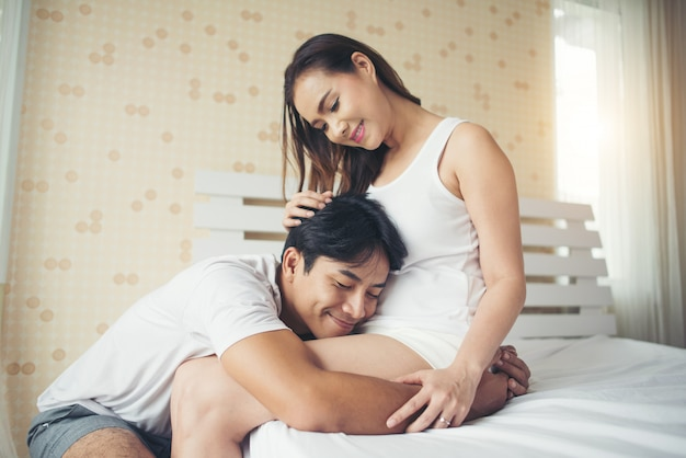 Father hearing his son or daughter kicking inside mother on the bed at home