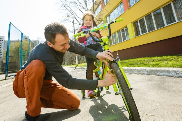 Father helped the daughter fall bike. riding bicycles on the street.healthy lifestyle concept