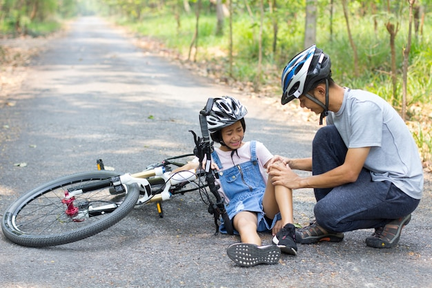 Father helped the daughter fall bike. riding bicycles on the street.