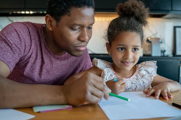 Отец помогает и поддерживает свою дочь с домашним обучением, оставаясь дома